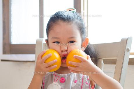 オレンジで顔を挟んでいる女の子 FYI01077656