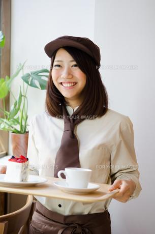 制服を着てカフェで働く女性 FYI01077659