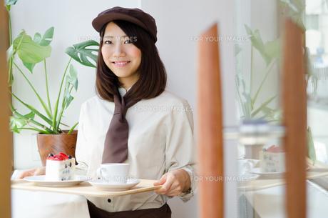 制服を着てカフェで働く女性 FYI01077668