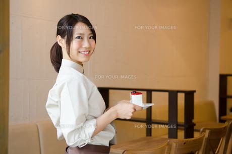 ケーキを持っているカフェの店員 FYI01077679