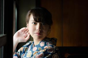 日本家屋の窓辺でこちらを見る着物姿の女性 FYI01077689