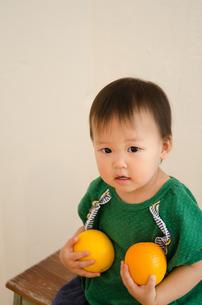 オレンジを両手で持っている女の子 FYI01077692