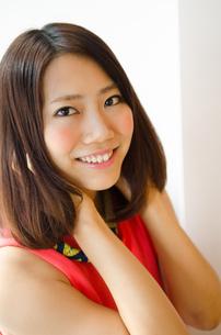 髪を触りながら笑っている女性 FYI01077701