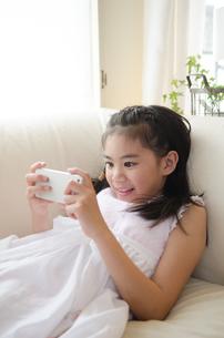 スマートフォンを楽しそうに操作している女の子 FYI01077733