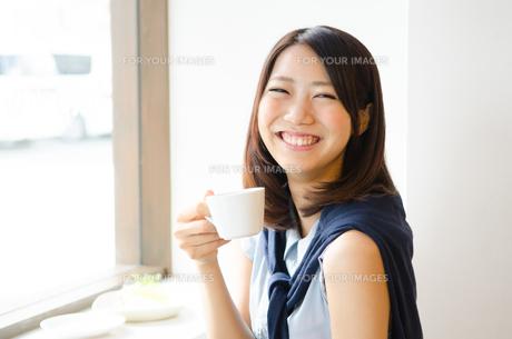 コーヒーカップを持って笑う女性 FYI01077741