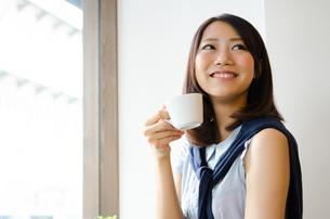 コーヒーカップを持って笑う女性 FYI01077742