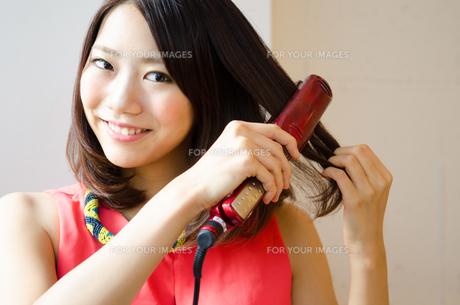 ヘアアイロンで髪の毛をセットしている女性の素材 [FYI01077747]