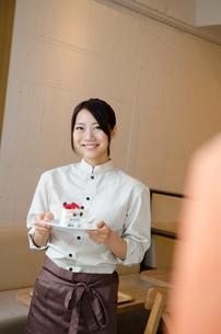 ケーキを持っているカフェの店員 FYI01077749