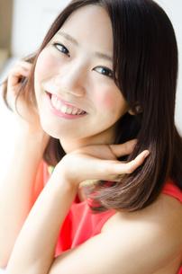 髪を触りながら笑っている女性 FYI01077761