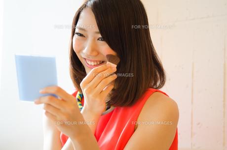 鏡を見ながらメイクを直している女性 FYI01077776