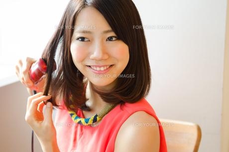 ヘアアイロンで髪の毛をセットしている女性 FYI01077777