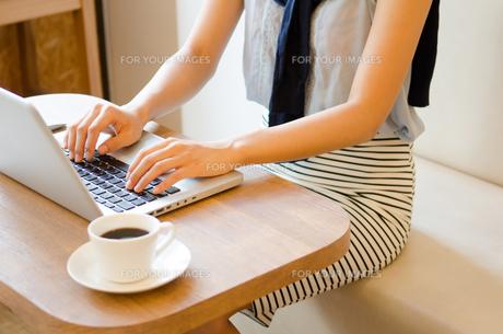 カフェでノートパソコンで仕事をしている女性の手元 FYI01077786