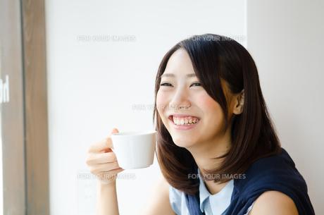 コーヒーカップを持って笑う女性 FYI01077795