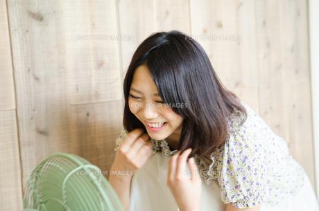 扇風機に向かって笑っている女性 FYI01077885