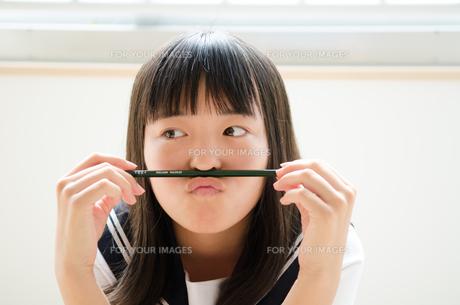 鉛筆を鼻の下に挟んでいる制服姿の女の子 FYI01077886