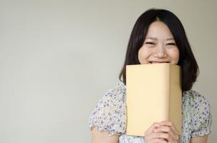 本を持って笑っている女性 FYI01077892
