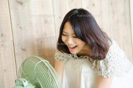 扇風機に向かって声を出している女性 FYI01077906