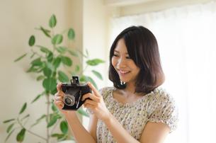 クラシックカメラを見ている笑顔の女性 FYI01077987