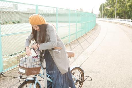 自転車の荷物を触っている女性 FYI01078007