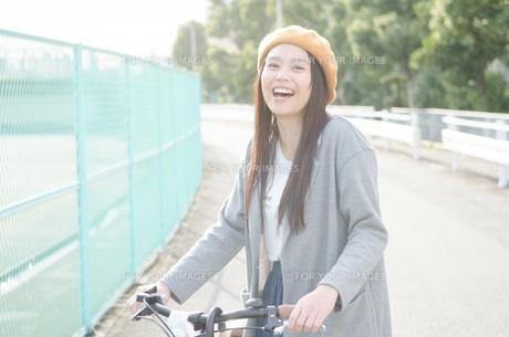 自転車のハンドルを持って笑っている女性 FYI01078070