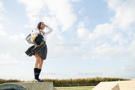 立って遠くを見ている女子学生 FYI01078072