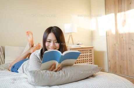 ベッドで本を読んでいる女性 FYI01078091