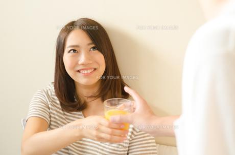 オレンジジュースを受け取る女性 FYI01078102
