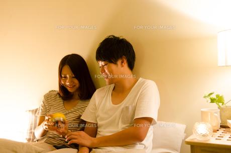ベッドで目覚まし時計をセットするカップル FYI01078103