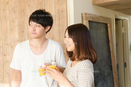 オレンジジュースを持っているカップル FYI01078107