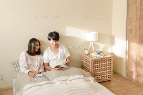 ベッドの上で本を読むカップル FYI01078110