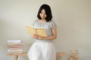 ベンチに座って本を読んでいる女性 FYI01078120