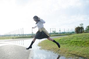 水たまりをジャンプする女子学生 FYI01078121