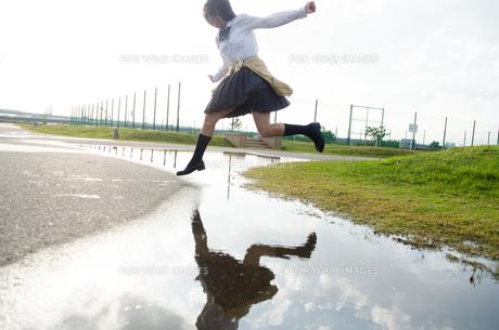 水たまりをジャンプする女子学生 FYI01078130