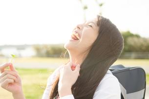 クローバーを持って笑う女子学生 FYI01078131