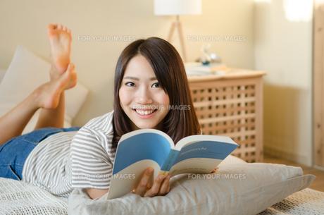 ベッドで本を読んでいる笑顔の女性 FYI01078150
