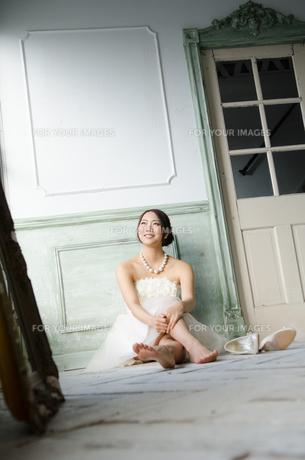 白いドレスを着て床に座る女性の素材 [FYI01078152]