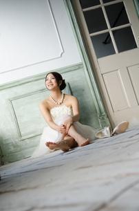 白いドレスを着て床に座る女性 FYI01078156