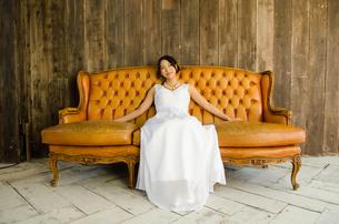 大きなソファに座るドレス姿の女性 FYI01078165