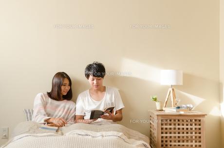 ベッドの上で本を読むカップル FYI01078168