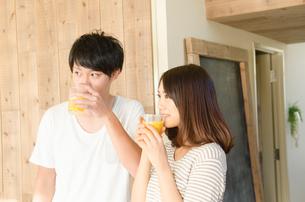 オレンジジュースを飲むカップル FYI01078170