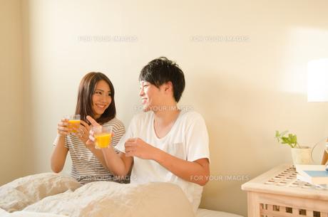 ベッドでオレンジジュースを持っているカップル FYI01078171