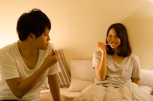 ベッドで歯を磨くカップル FYI01078175