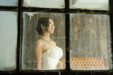 窓越しに見えるドレス姿の女性 FYI01078183