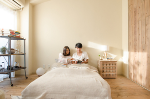 ベッドの上で本を読むカップル FYI01078184