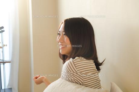 ベッドで笑う女性 FYI01078186