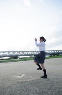 ボールを投げるふりをする女子学生 FYI01078192