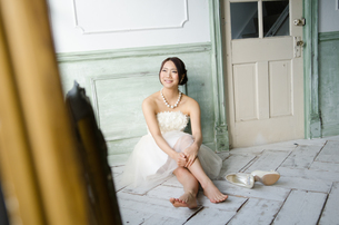 白いドレスを着て床に座る女性 FYI01078204