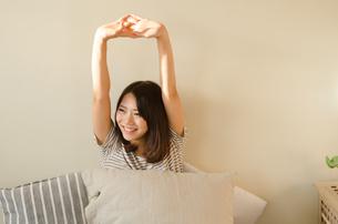 ベッドでストレッチをする女性の素材 [FYI01078207]
