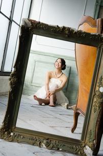 白いドレスを着て床に座る額縁越しの女性 FYI01078213