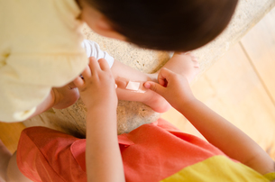 小さな子に絆創膏を貼っている女の子の手 FYI01078218